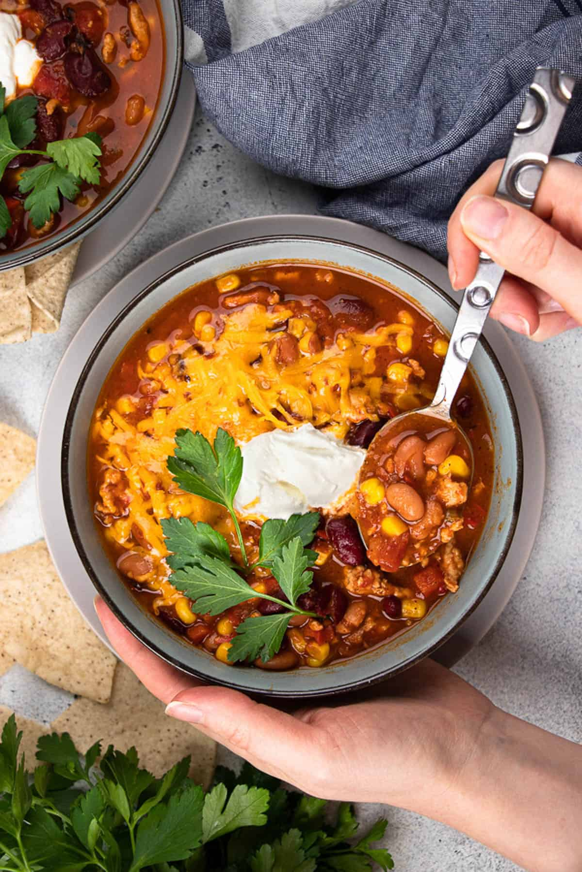 Turkey Chili, topped with sour cream, cheddar cheese, and cilantro in a blue bowl.
