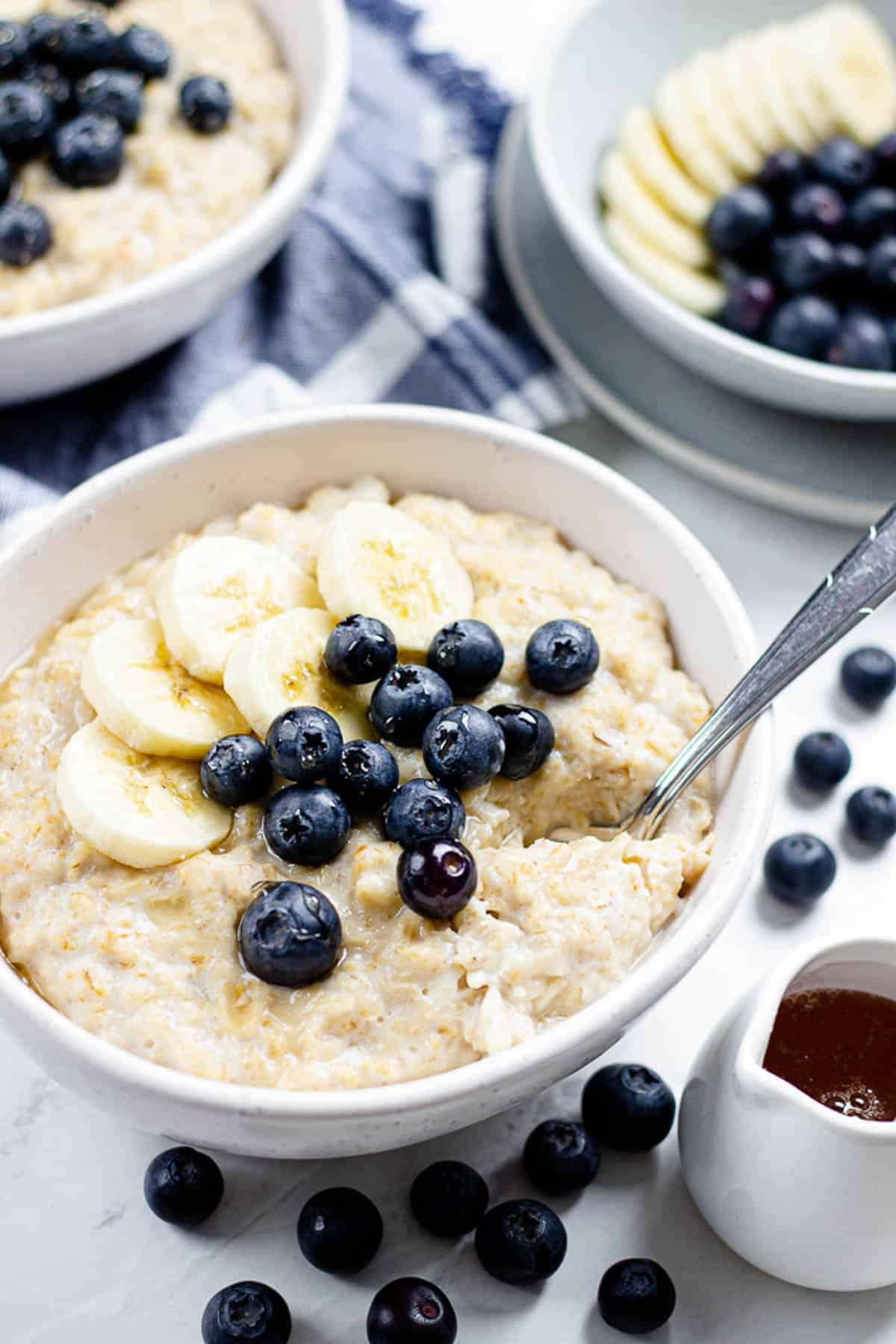 Oatmeal, topped with banana and blueberries in a bowl.