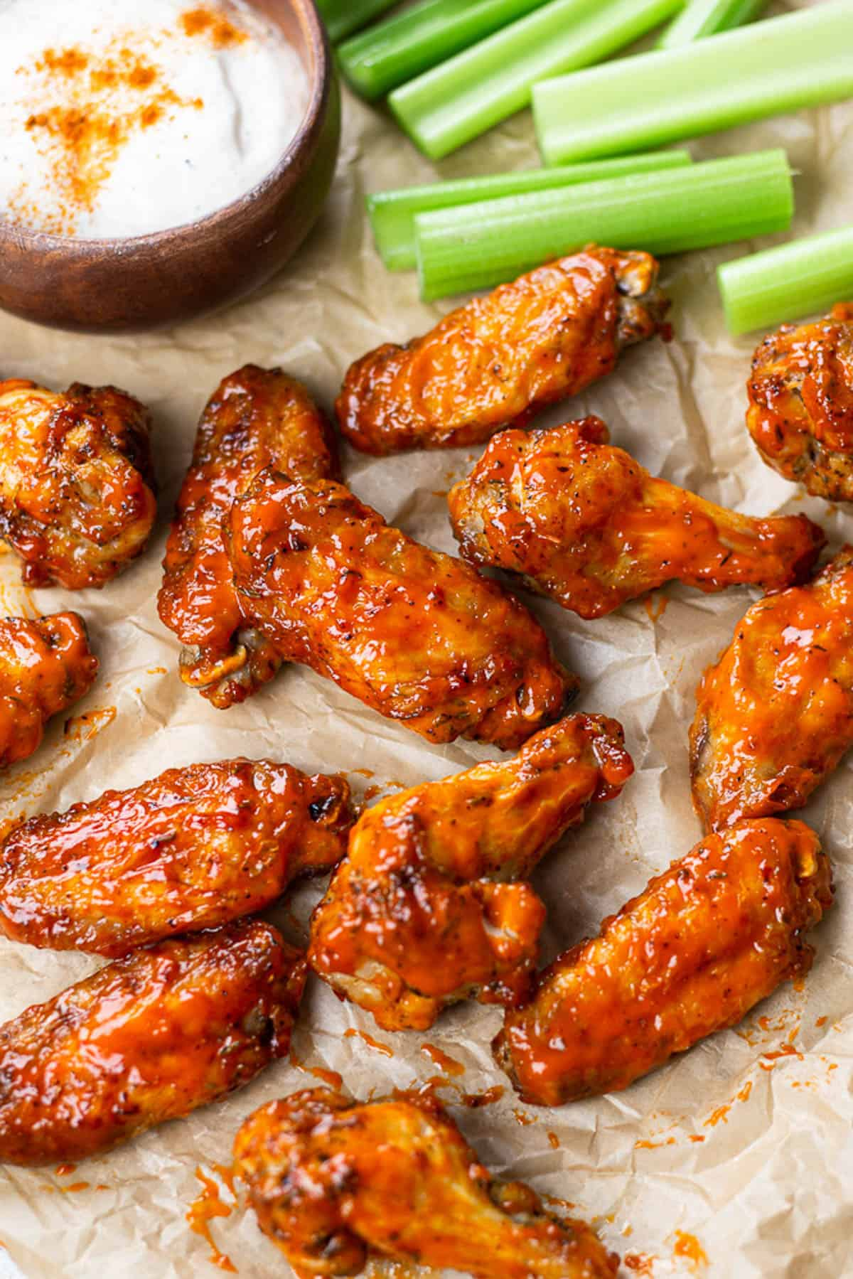 Buffalo wings on a parchment paper with ranch sauce and celery.