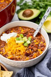 beef chilli, topped with sour cream, cheese, and avocado in a bowl.