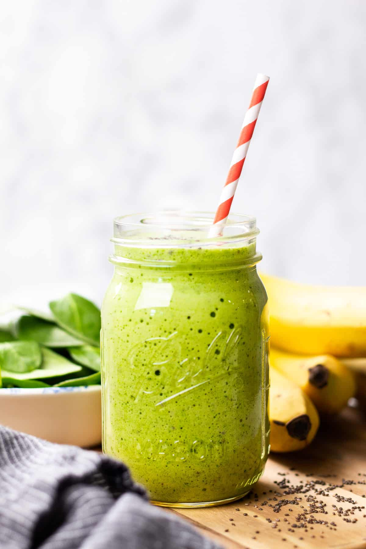 A close up photo of a green smoothie in a Mason jar.