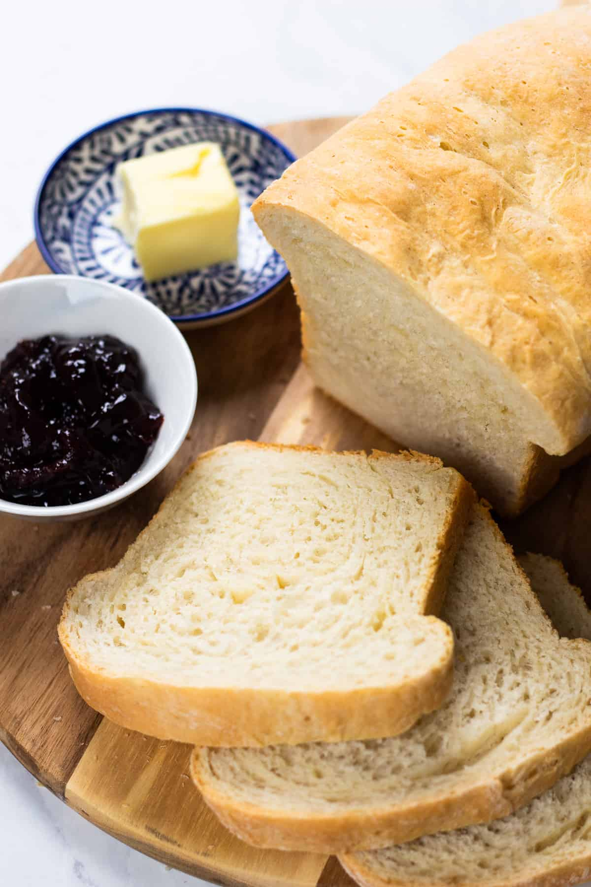 Sliced white bread on a board with butter and jam.