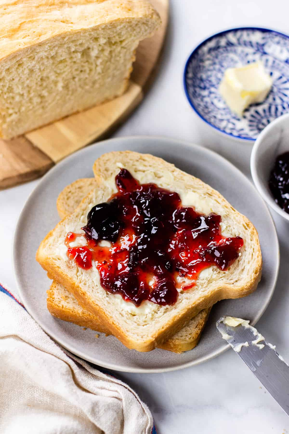 Two slices of bread, topped with butter and jam on a grey plate.