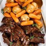 Pot Roast with potatoes and carrots served on a white plate.
