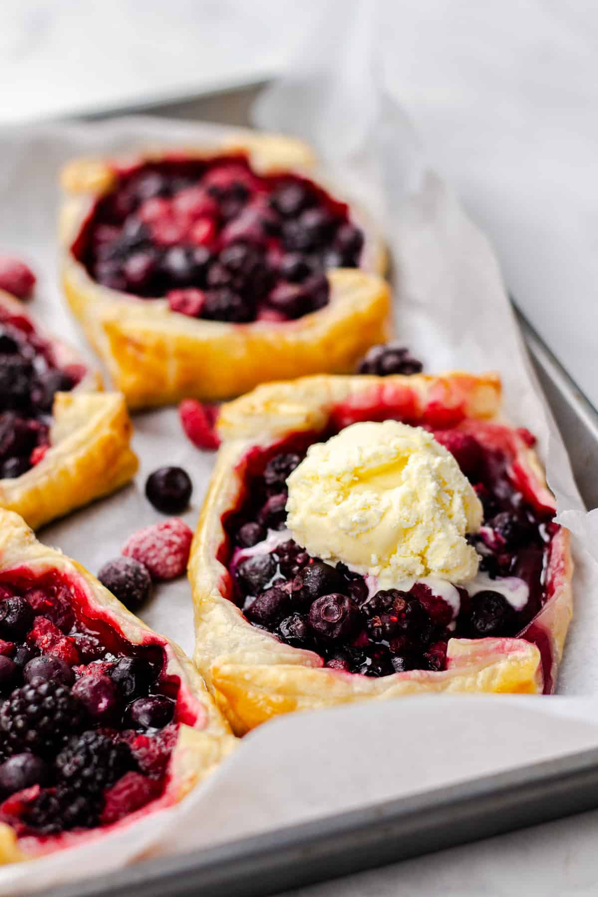 Mixed Berry Puff Pastry Tarts, topped with vanilla ice cream.