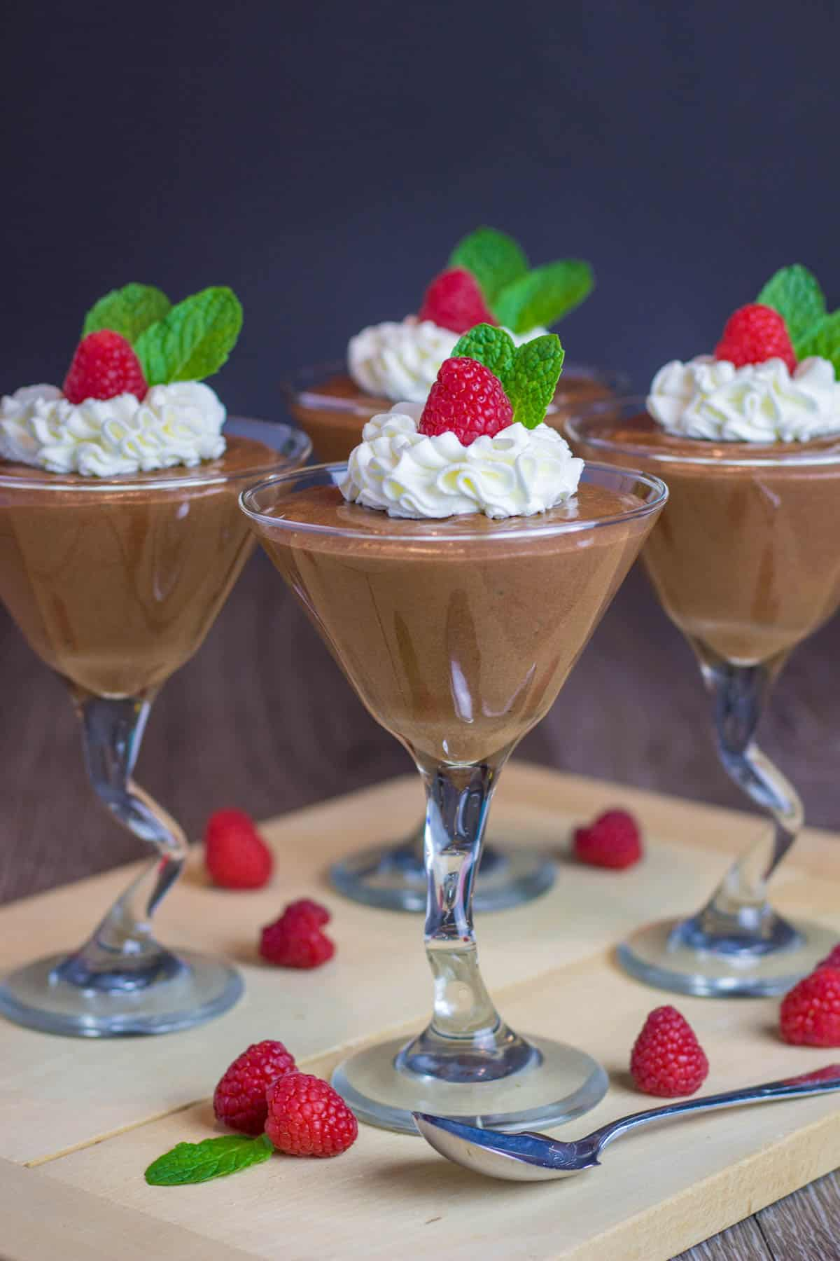 Chocolate mousse in a glass, toped with whipped cream and raspberry.
