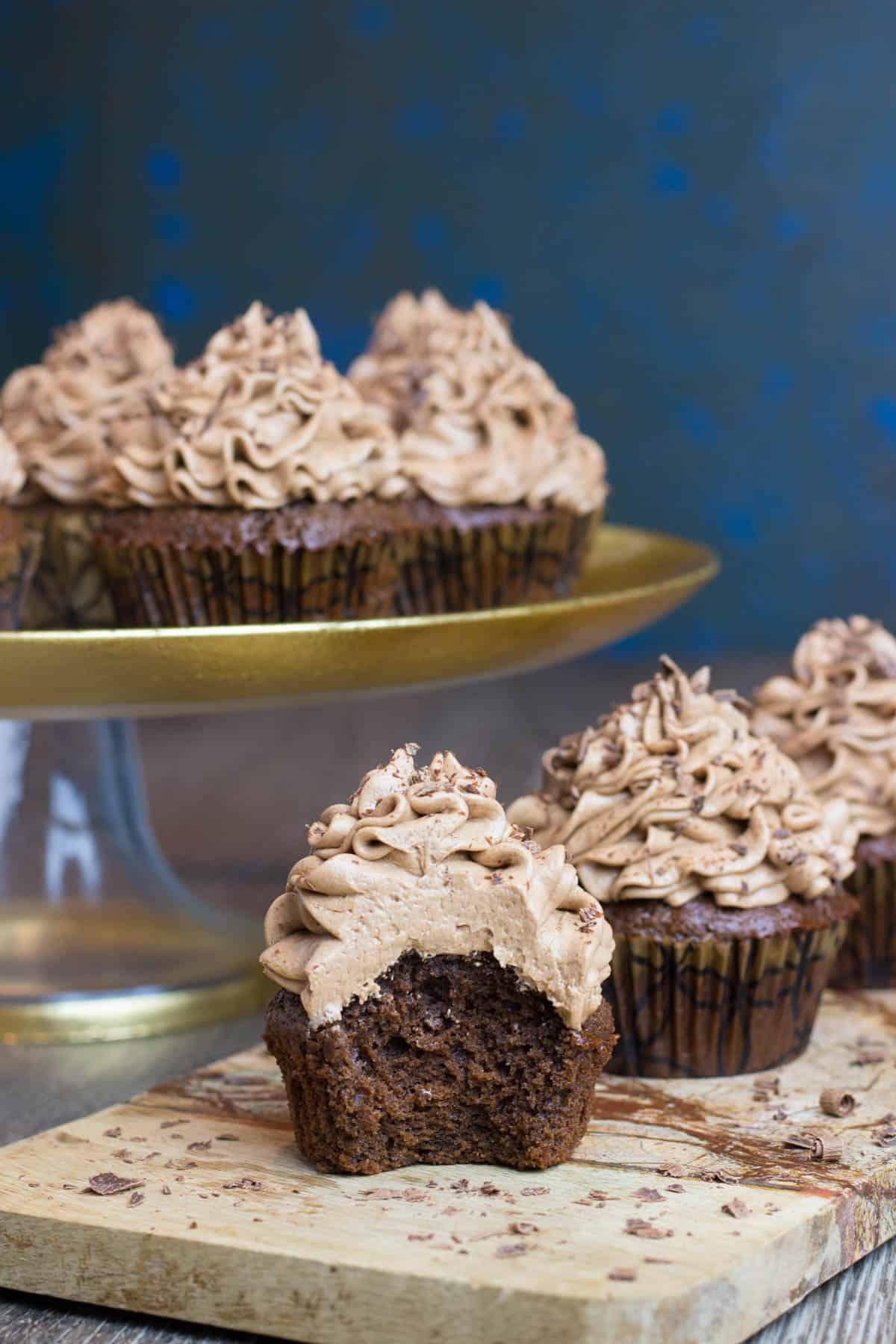 Kahlua Cupcakes toped with chocolate frosting on board.