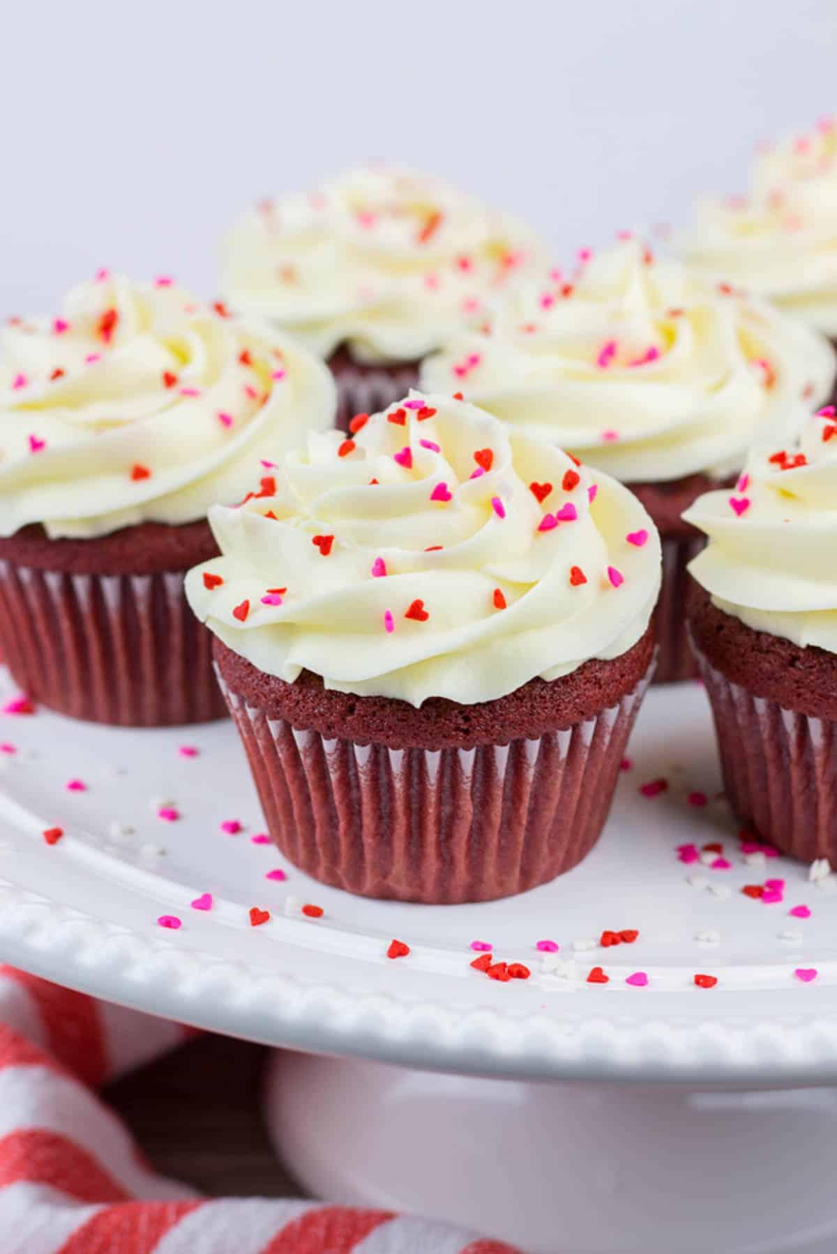 Red Velvet Cucakes topped with heart shaped sprinkles on a cake platter.