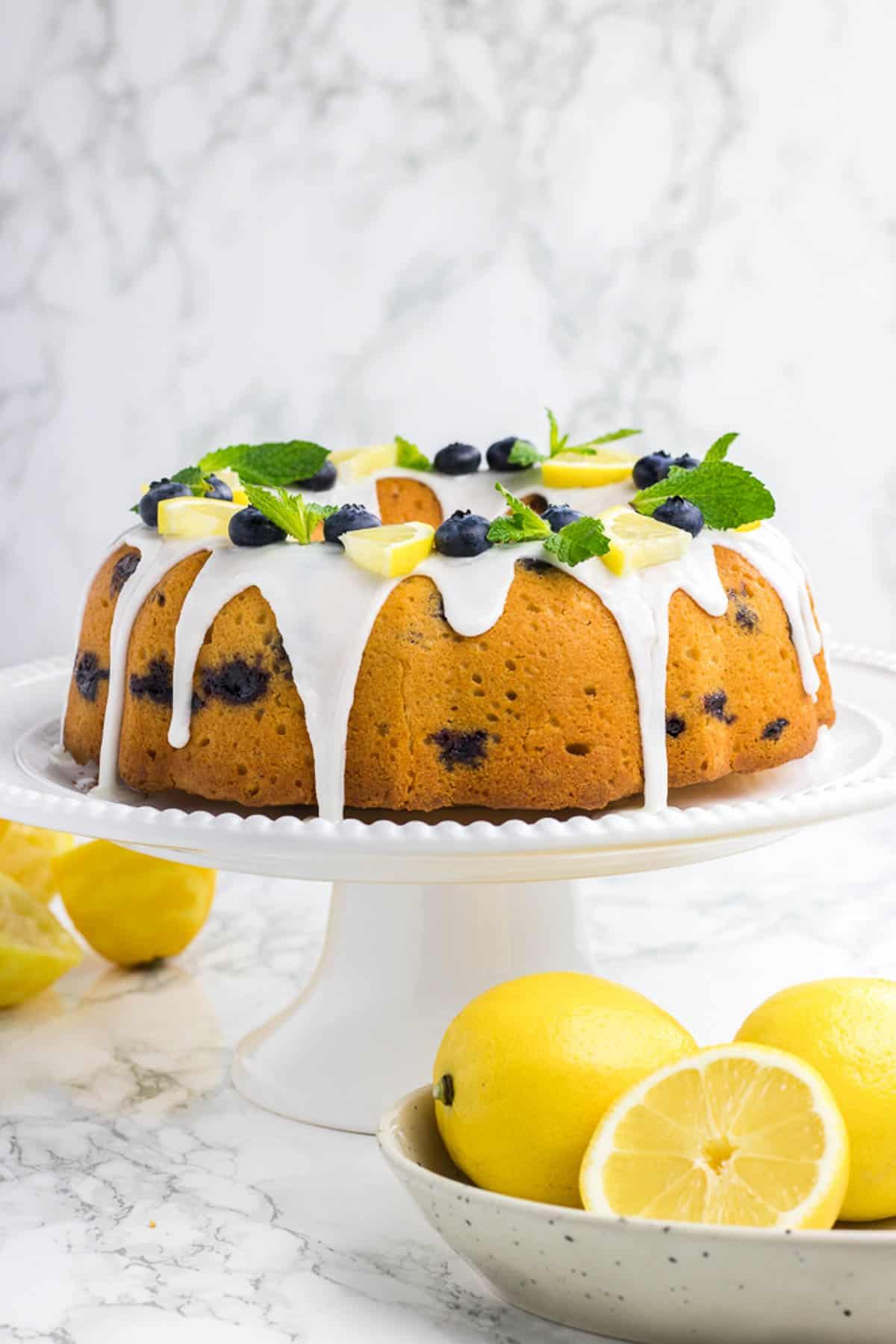 Lemon Blueberry Bundt Cake on a white cake platter.