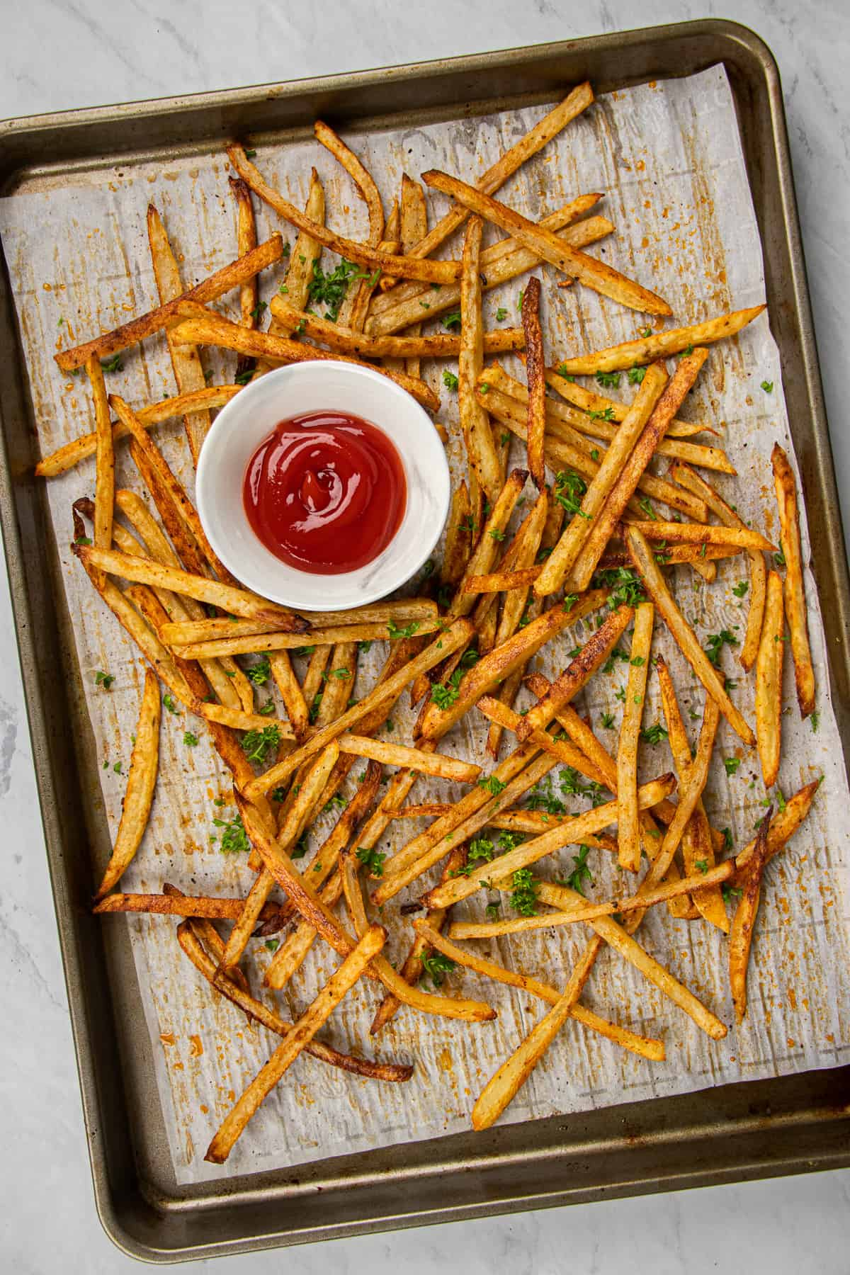 baked fries with ketchup on a baking sheet.