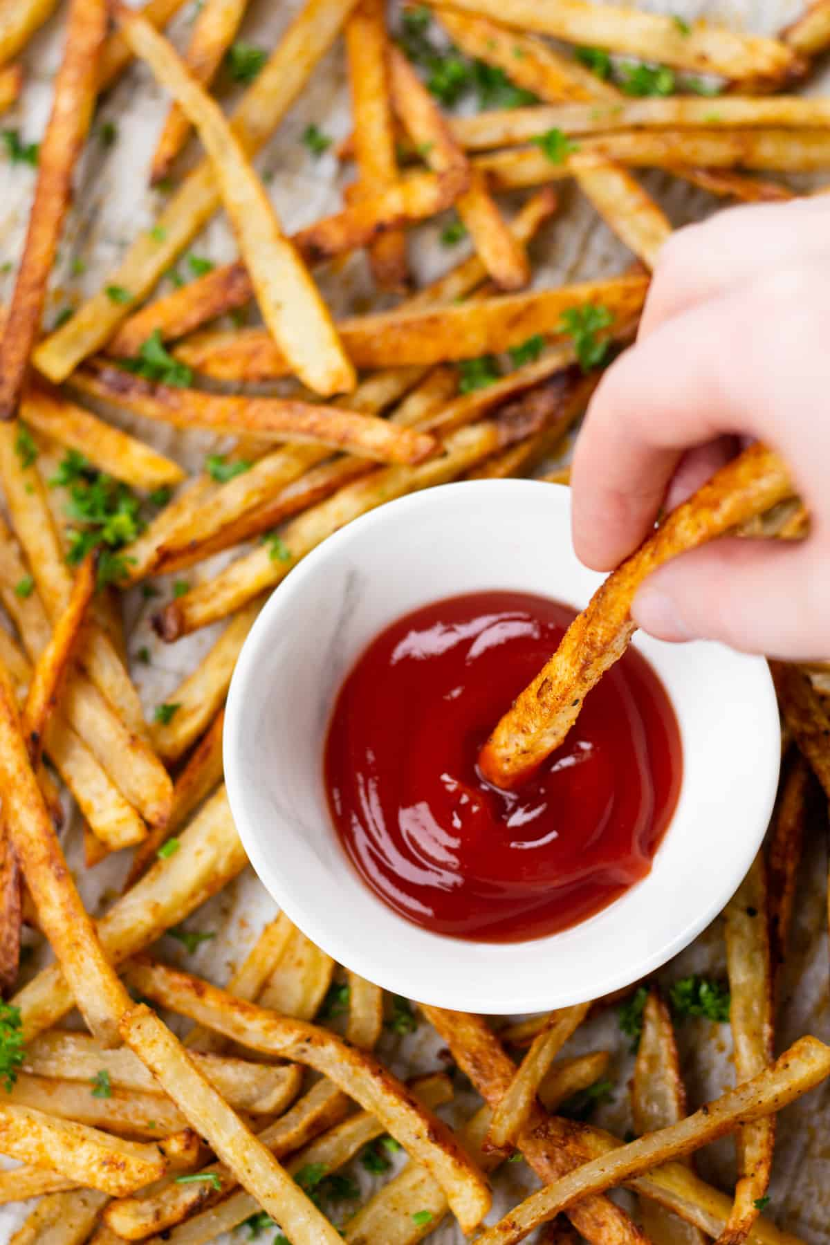 dipping baked fries in ketchup.