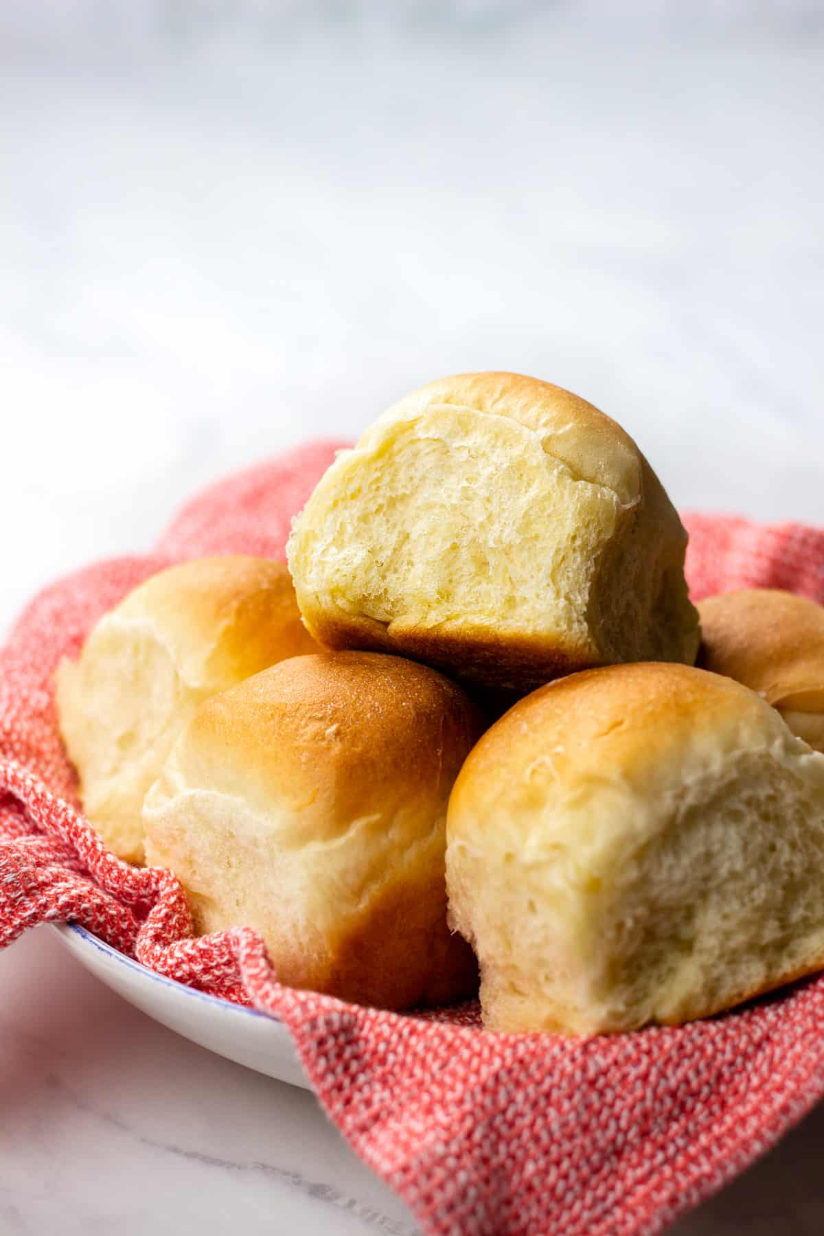 Dinner rolls on a red kitchen towel.