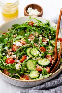 Farro salad with arugula, cucumbers, and tomatoes in a bowl.
