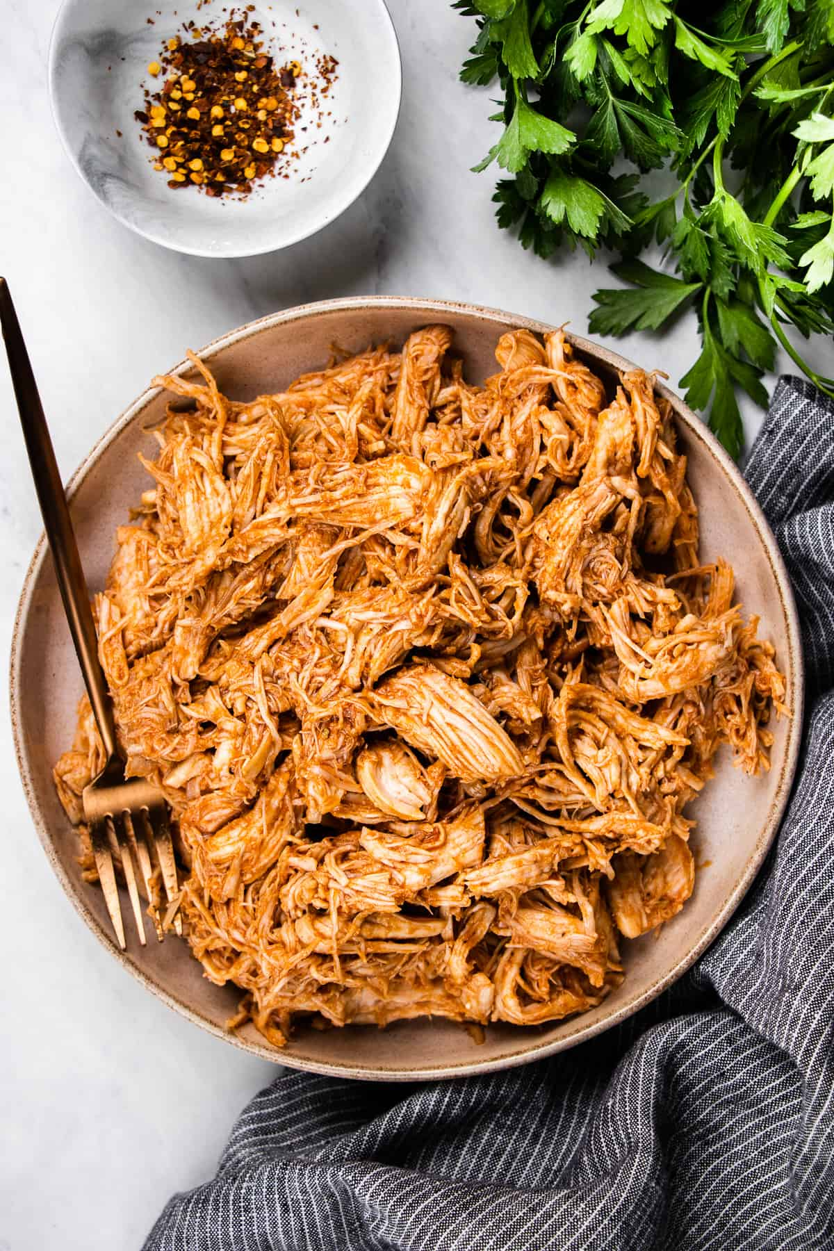 Pulled chicken in a bowl with a fork.