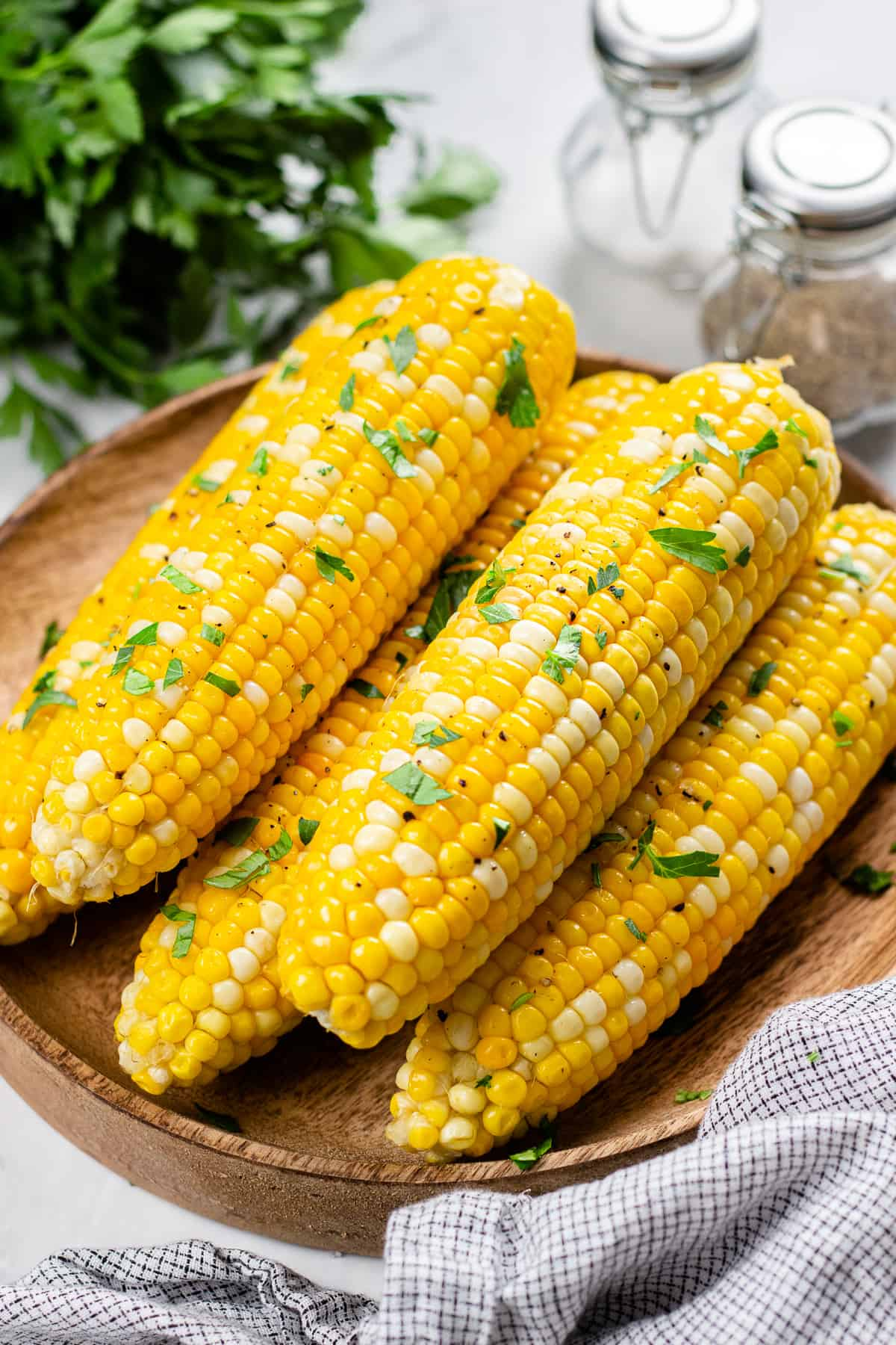Roasted corn, topped with chopped parsley, on a wooden plate.