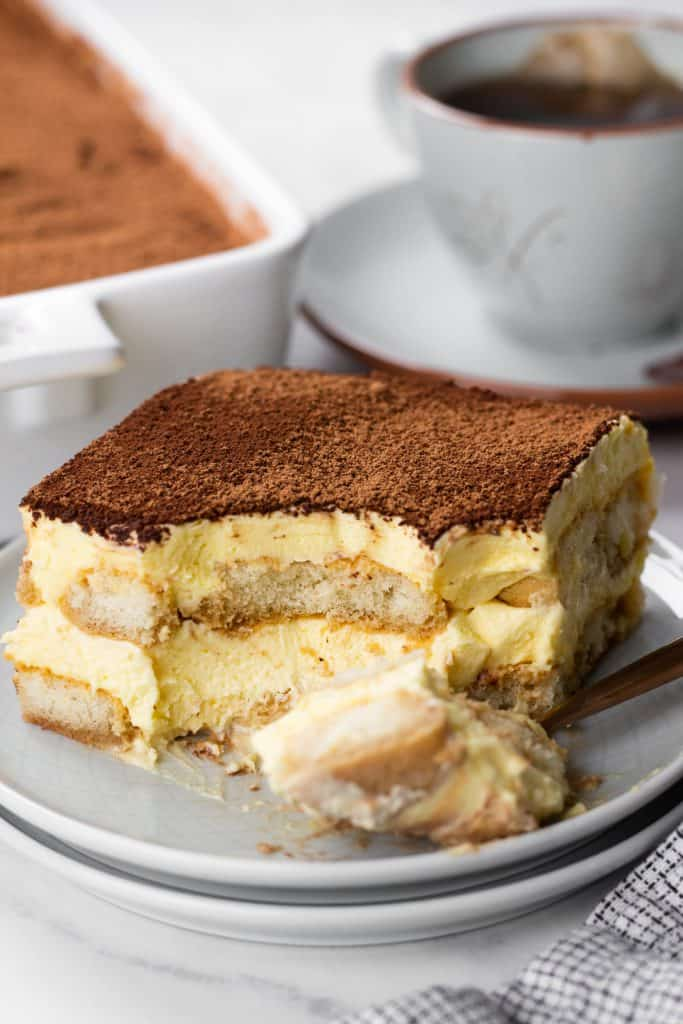 A slice of Tiramisu on a grey plate.