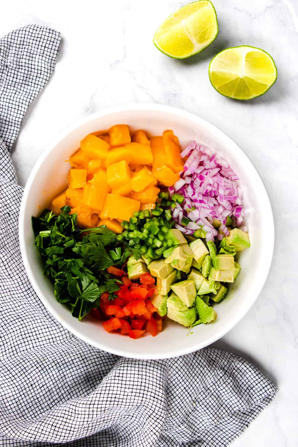 Chopped ingredients for mango salsa in a white bowl.