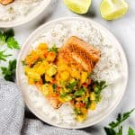 Salmon with Rice topped with mango salsa on a white plate.