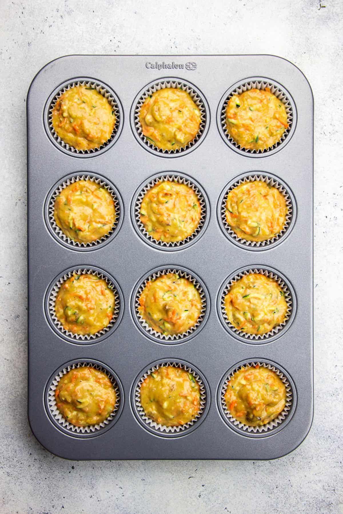 Carrot Zucchini Muffins batter in a muffin tin.