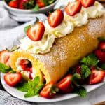 Strawberry Cake Roll decorated with whipped cream and fresh strawberries on a white oval plate.