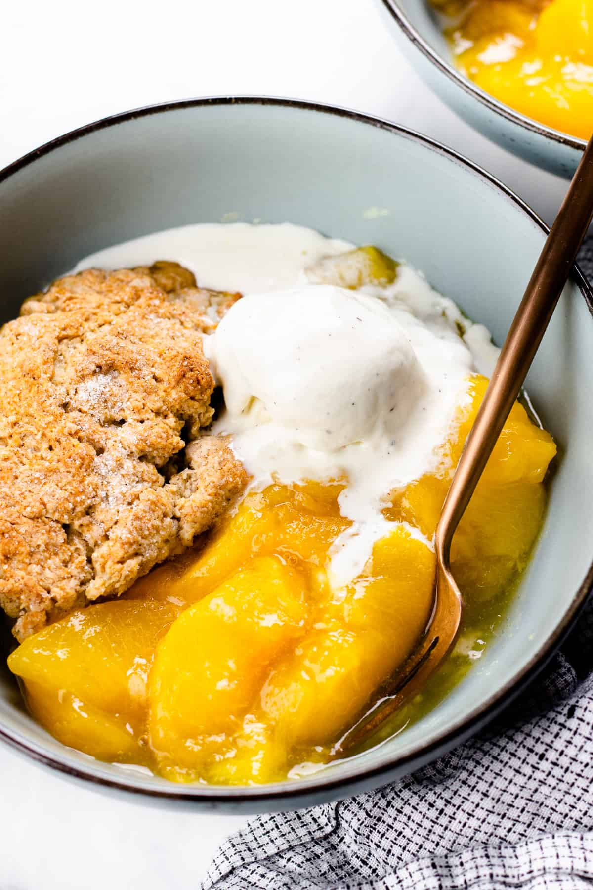 Peach Cobbler with a scoop of ice cream in a blue bowl.