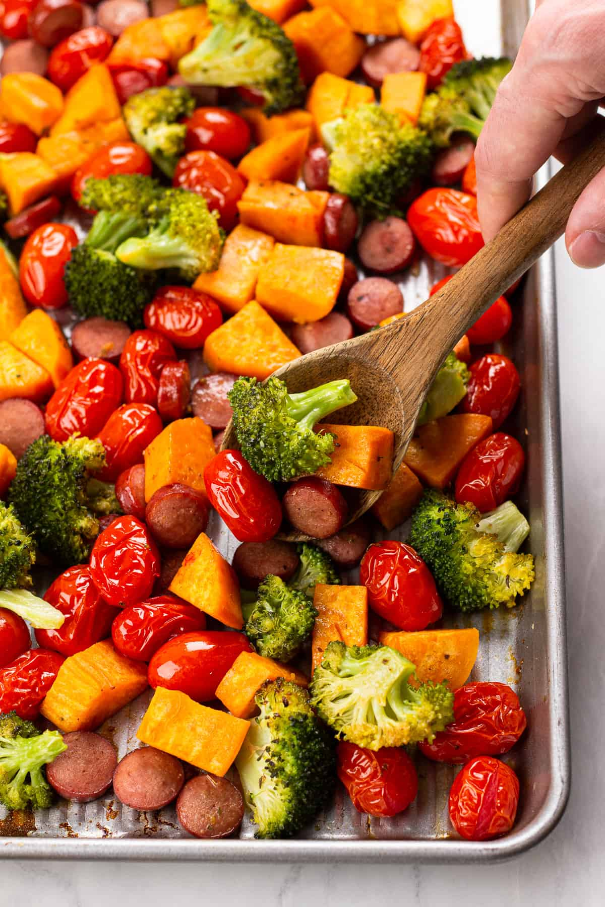 A wooden spoon scoops out roasted vegetables from a sheet pan.