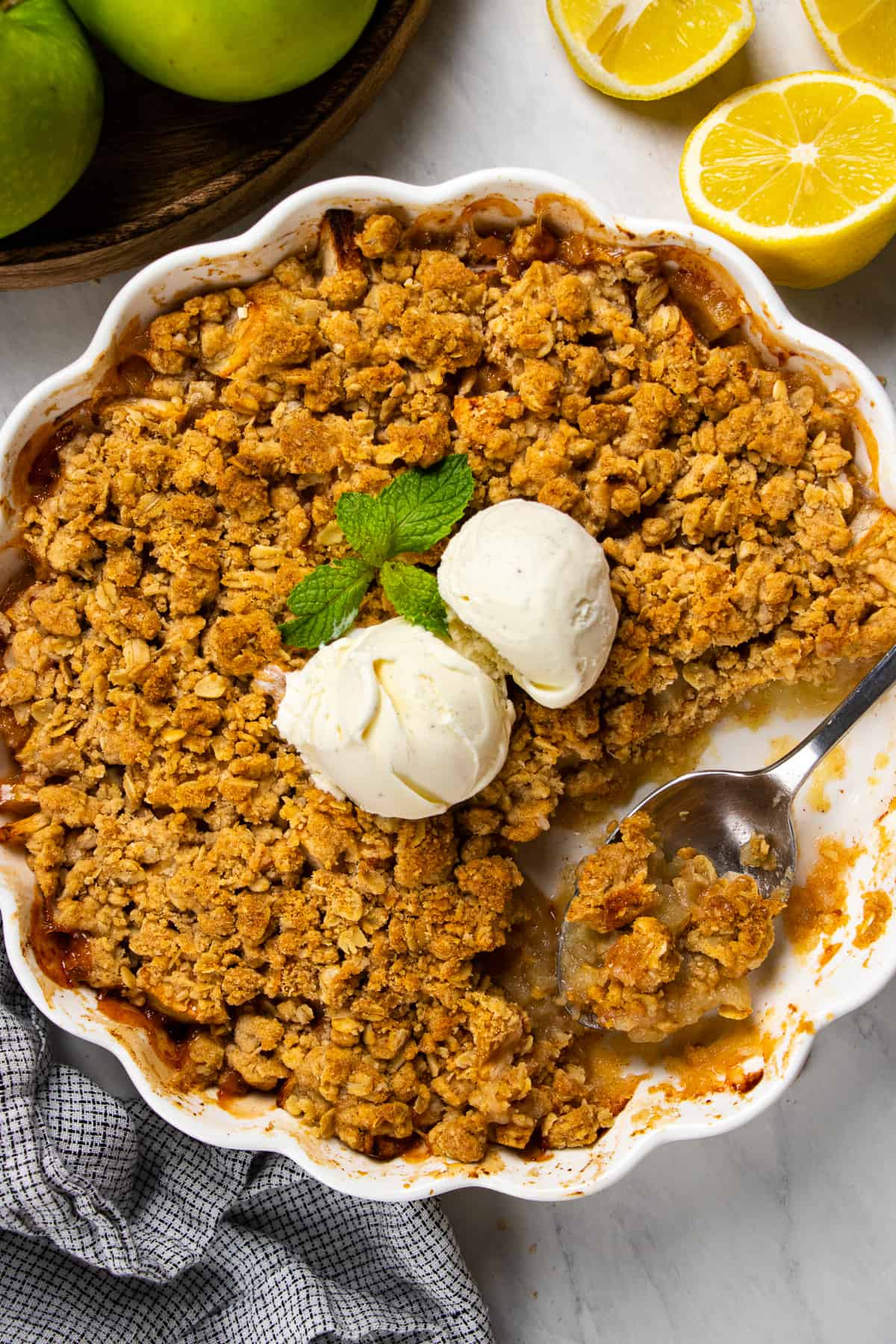 Overhead photos of apple crisp in a white baking pan with a scoop of ice cream on top.