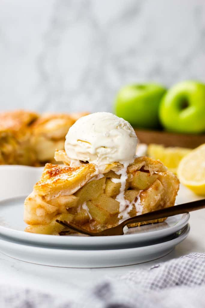 A slice of an Apple Pie wiht a scoop of ice cream on top.