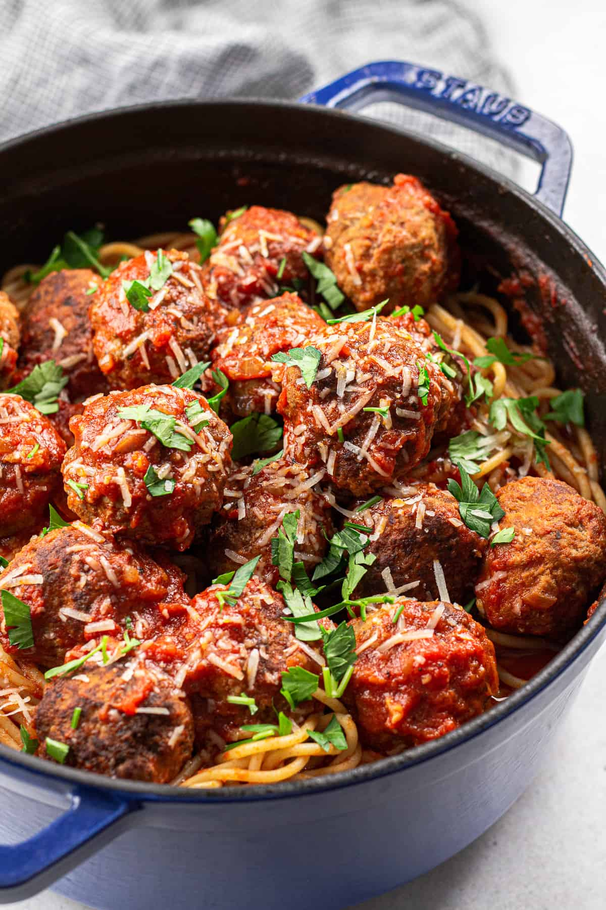 Spaghetti with meatballs, topped with parmesan and chopped parsley, in Dutch Oven.