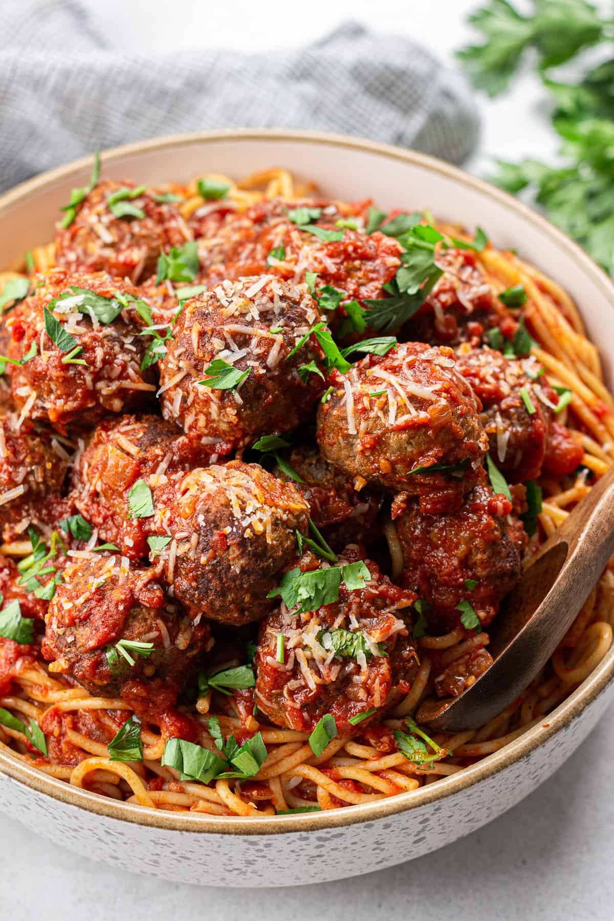 Spaghetti with meatballs, topped with parmesan and chopped parsley, in a large bowl.