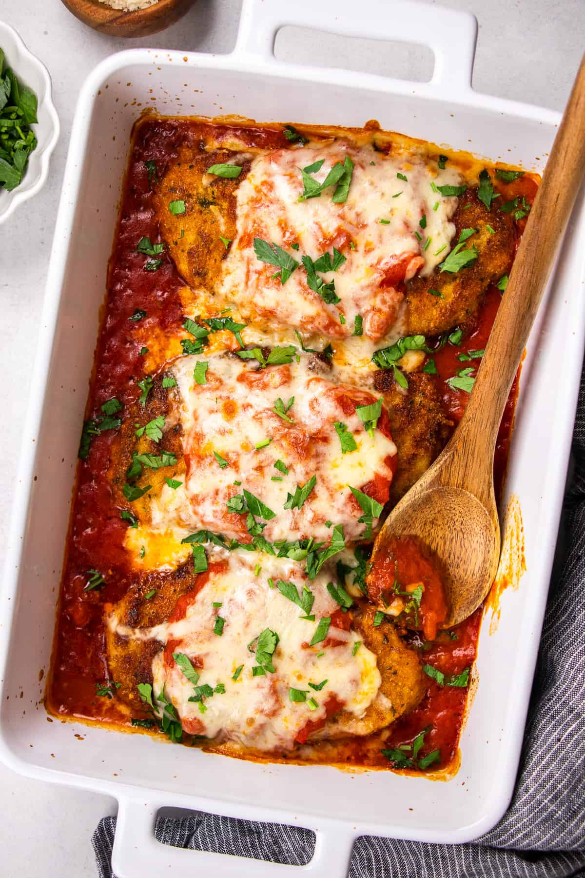 Chicken Parmesan with marinara sauce in a white baking pan.