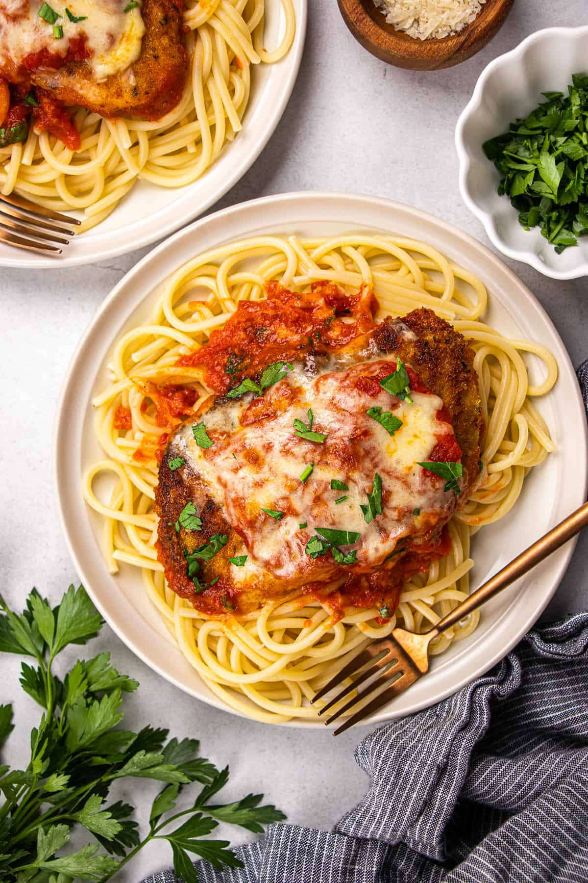 Chicken Parmezan with spaghetti on a white plate.