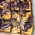 Cheesecake brownies, cut in small squares, laying on a parchment paper.