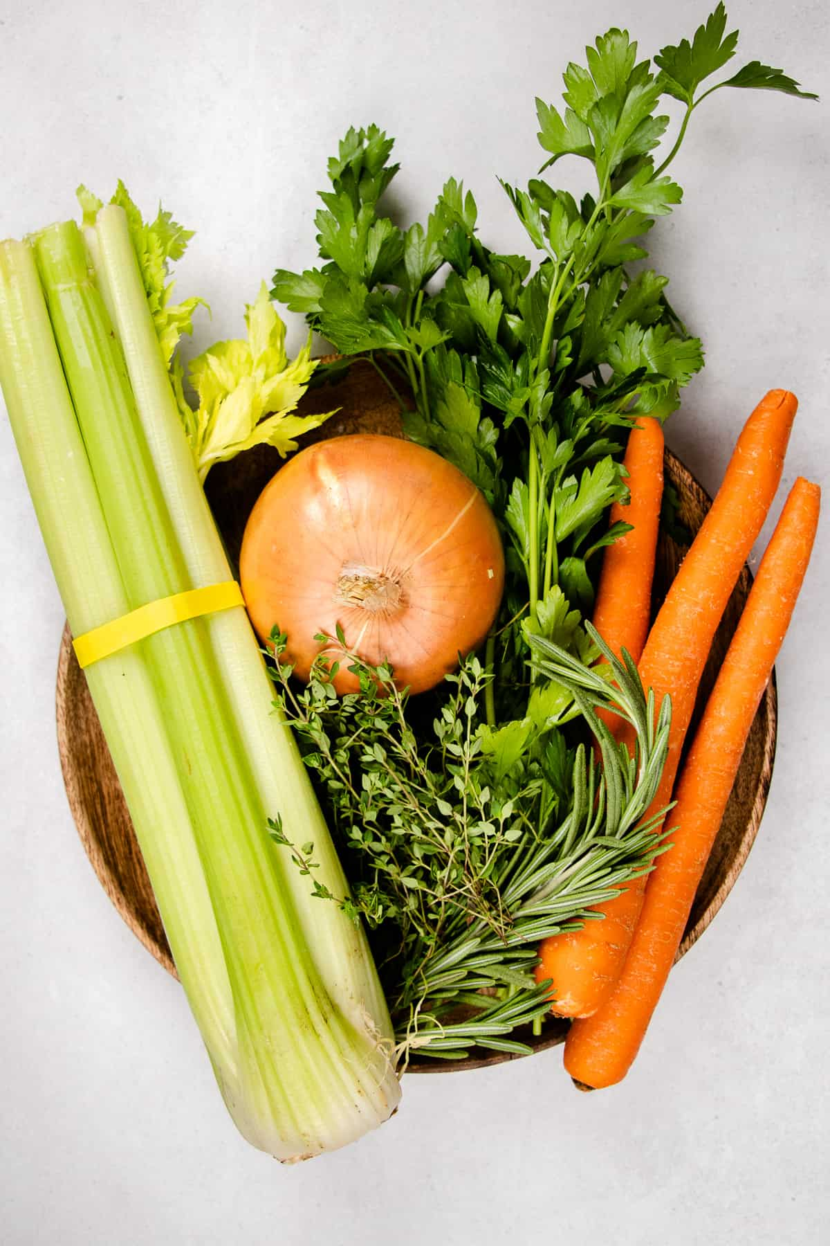 Celety, carrots, onion, parsley on a wooden plate.