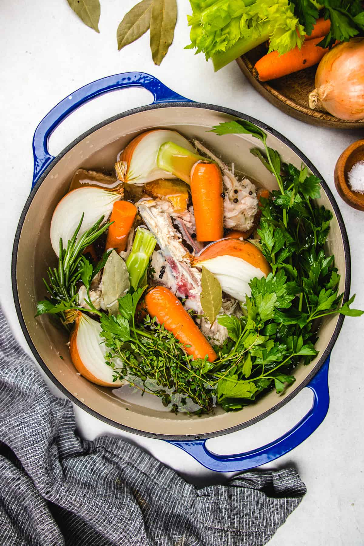 Chicken carcass, chopped onion, carrots, celery, parsley in a blue pot.