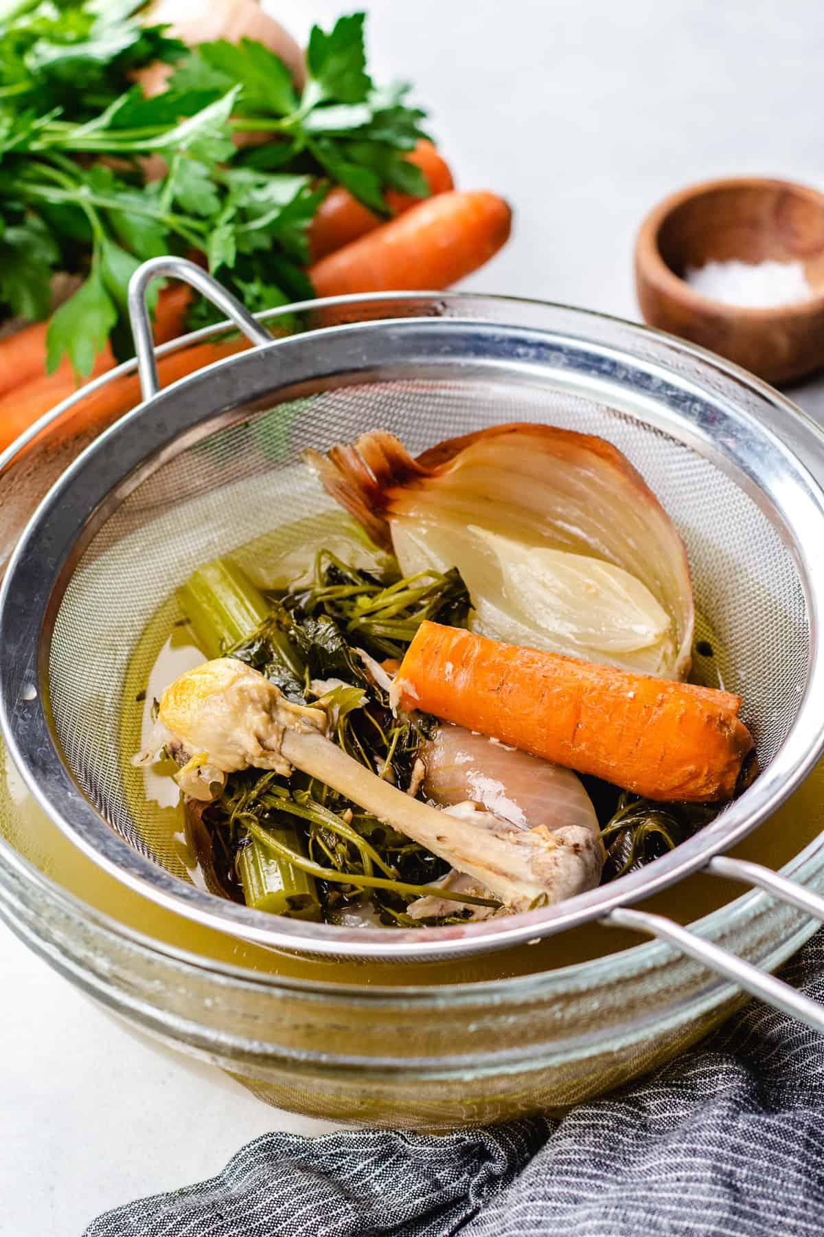 Cooked chicken bones with vegetables in a mesh to strain chicken stock.