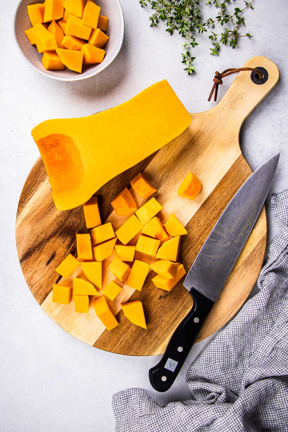 A half of butternut squash and some cubed squash with a knife on a round cutting board.