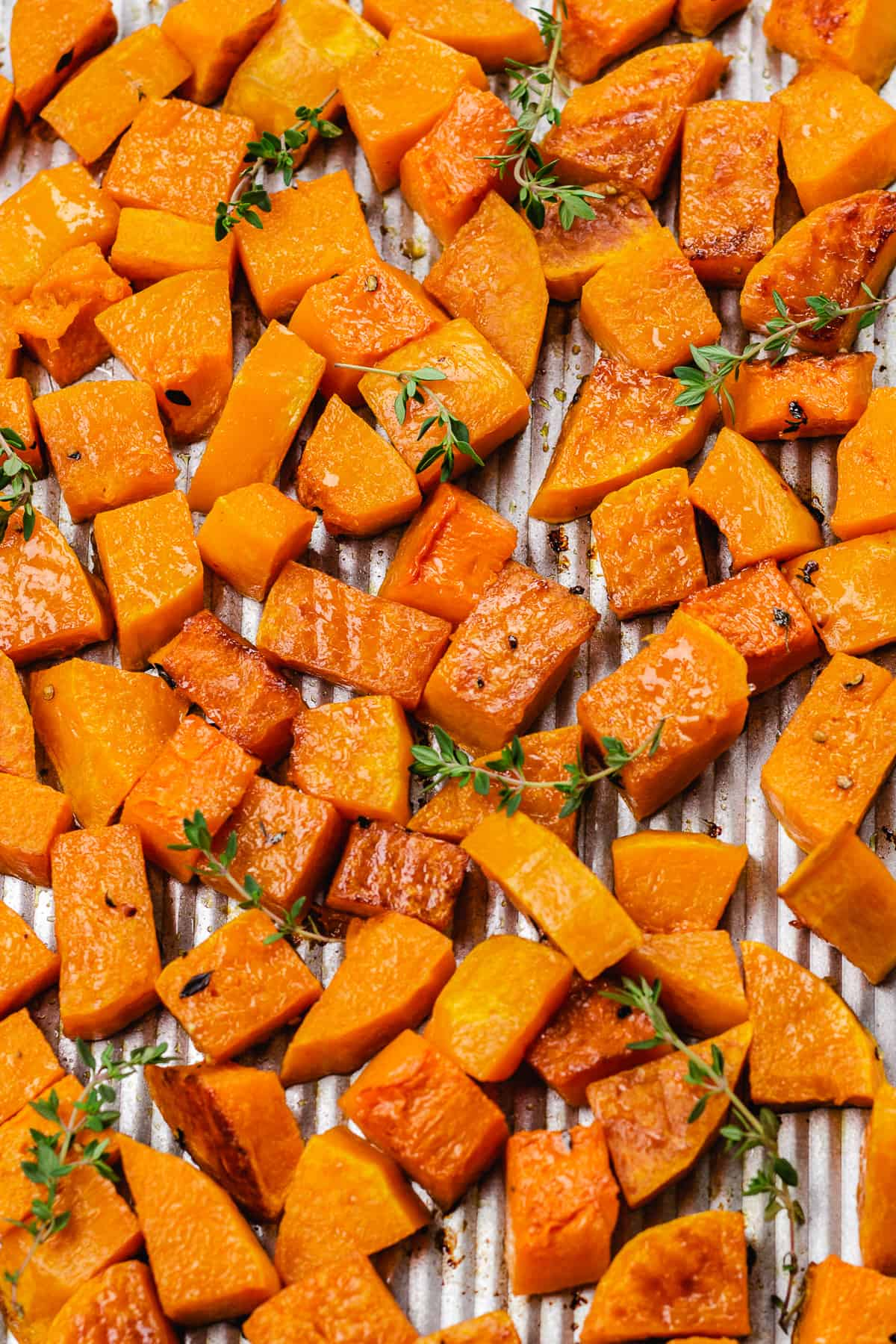 Cubed and Roasted Butternut Squash topped with thyme on a baking sheet.