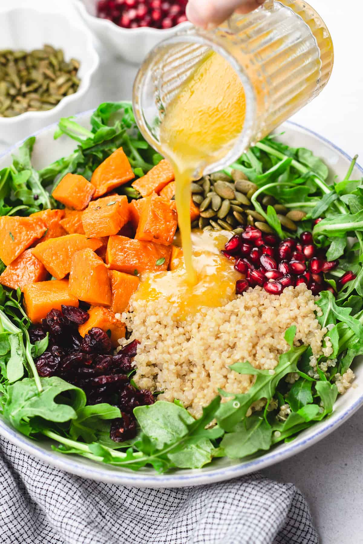 Pouring vinaigrette into a bowl with Butternut Squash Quinoa Salad.