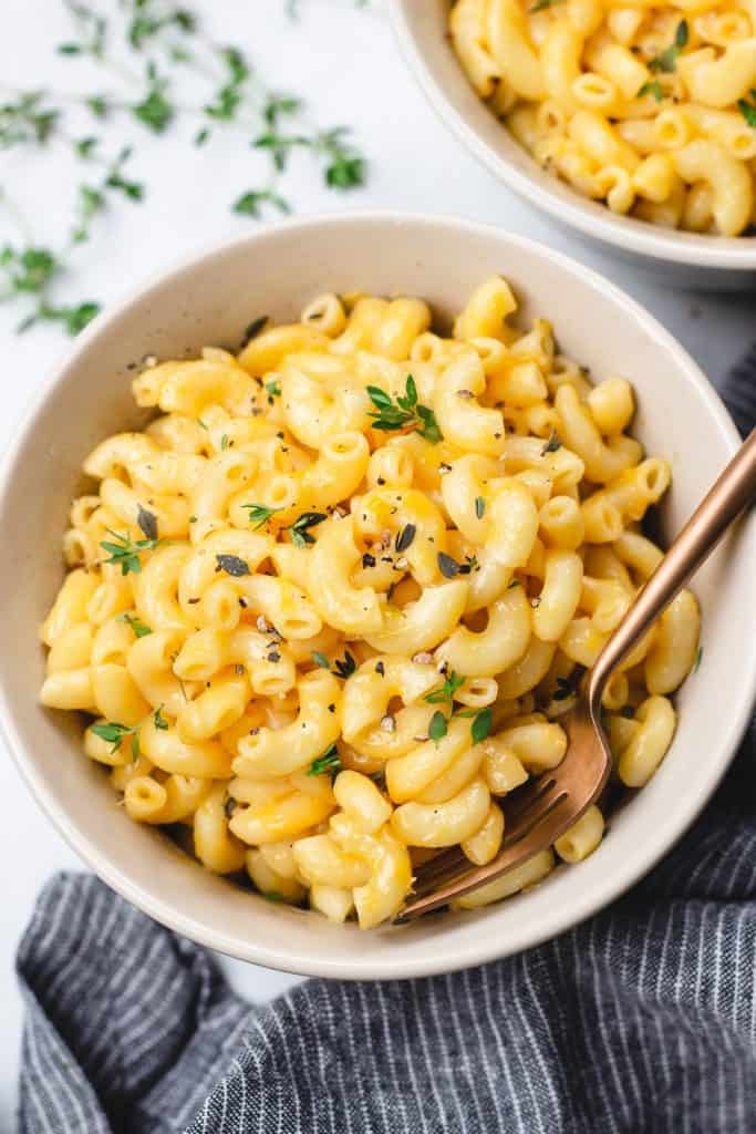 Mac and Cheese topped with thyme and black pepper in a bowl with a fork.