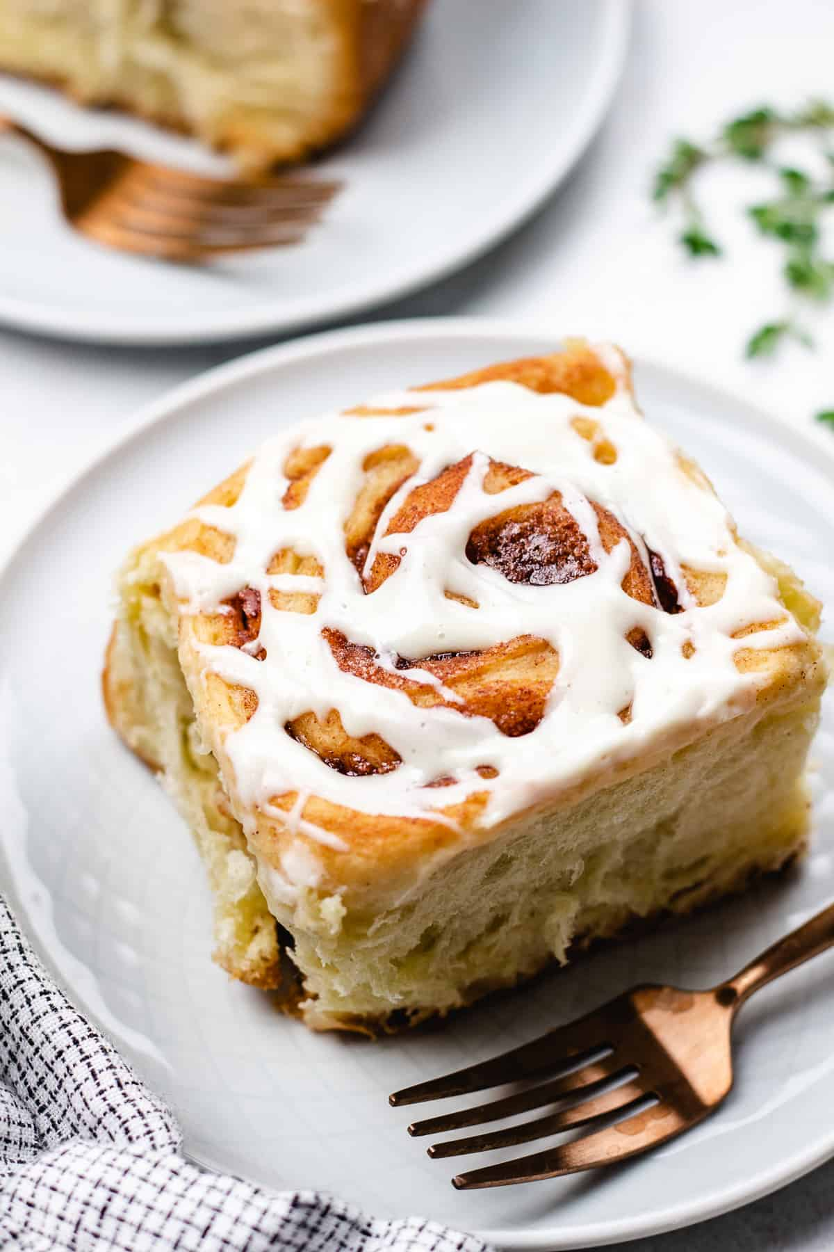 Cinnamon roll with glaze on a grey plate with a fork.