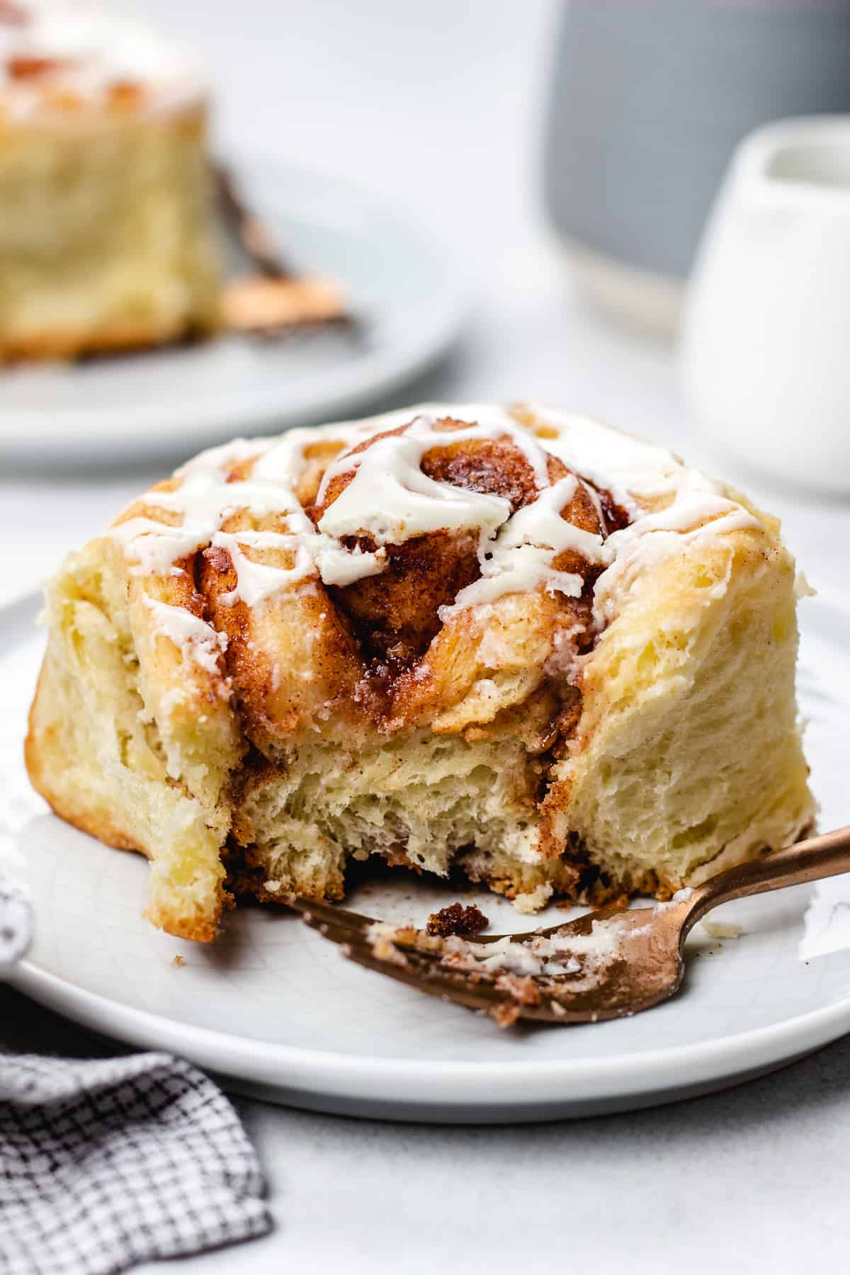 Cinnamon roll topped with icing on a plate with a fork.