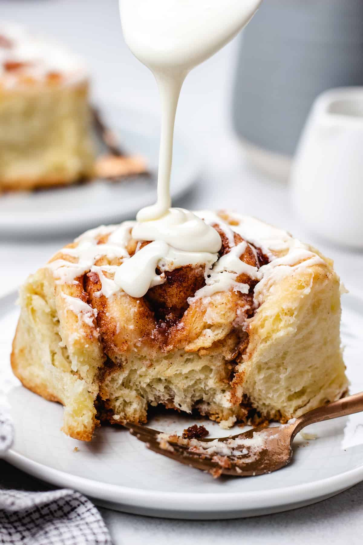 Pouring cream cheese icing over cinnamon roll.