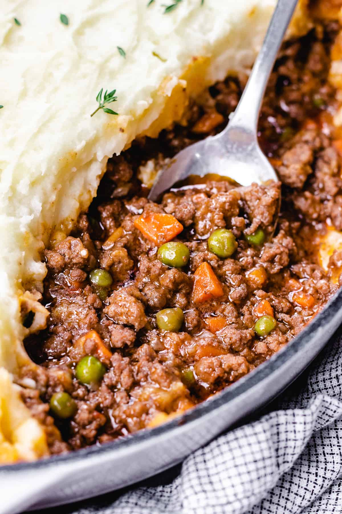 Shepherd's Pie in a white casserole with a spoon scooping out.