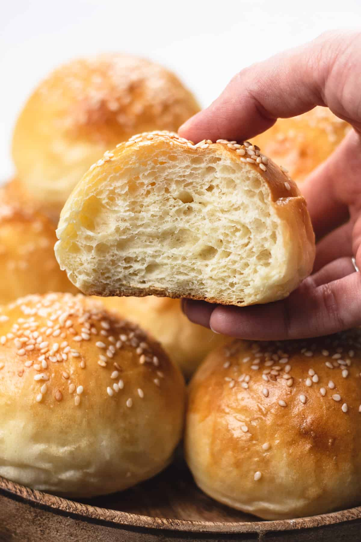 A close up photo of potato rolls topped with sesame seeds.