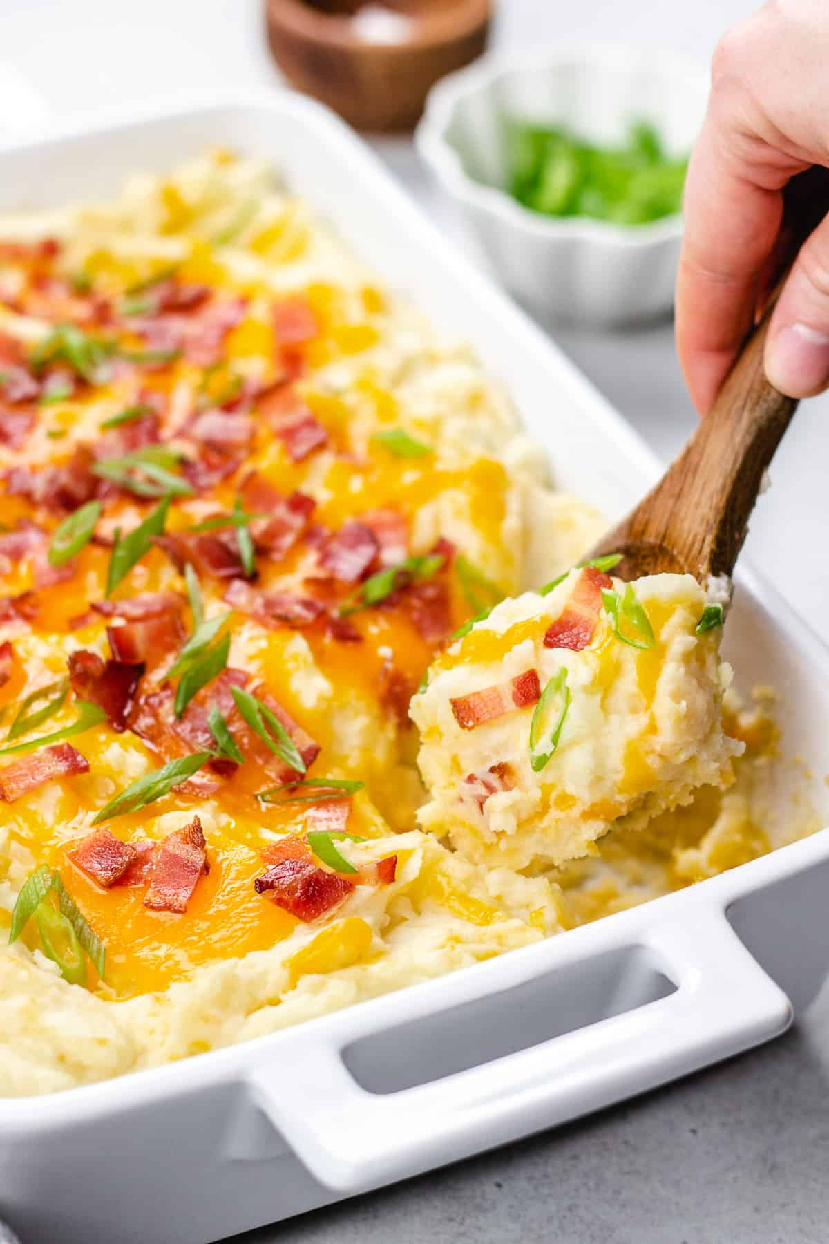 Scooping out mashed potatoes with cheese and bacon with a wooden spoon.