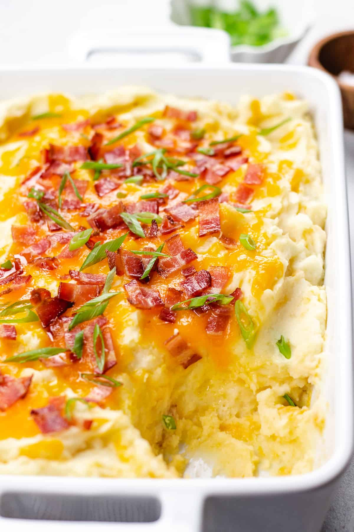 Mashed potatoes topped with cheese and bacon in a white casserole.