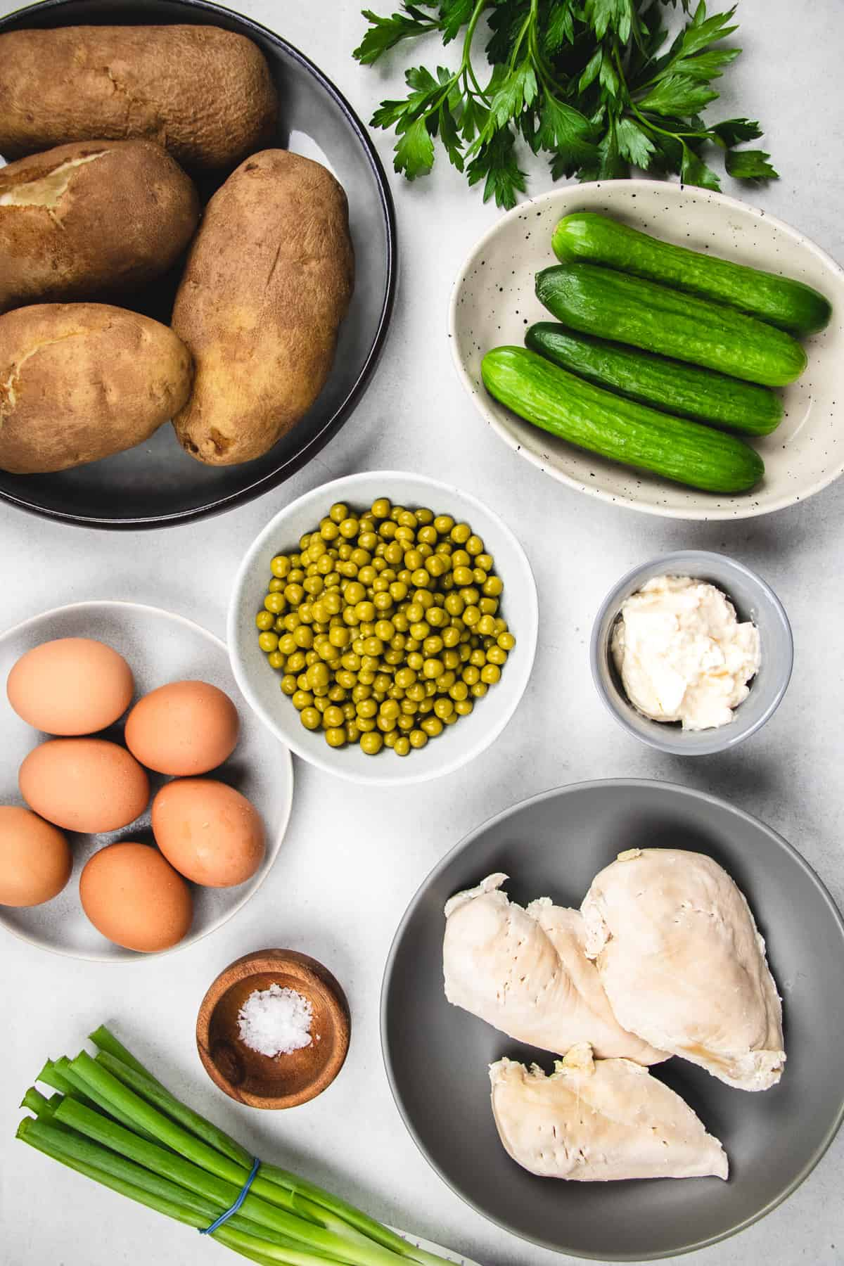 Ingredients for Olivie salad (chicken, potatoes, eggs, peas, cucumbers, green onion, parsley, and salt).