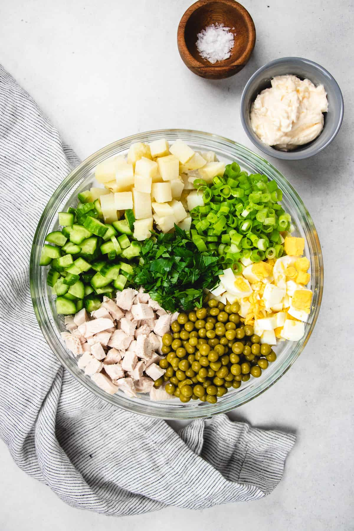 Chopped ingredients for Olivie salad in a clear bowl.