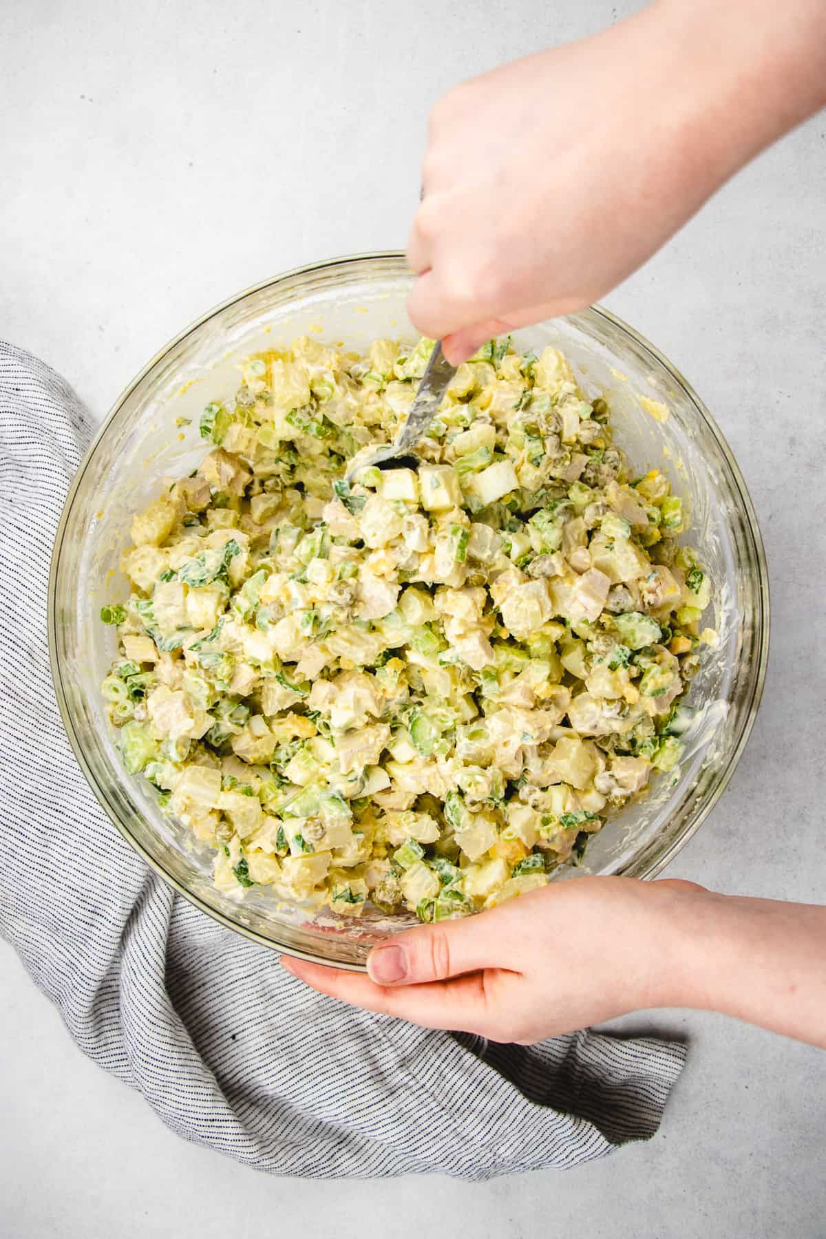Mixing Olivie salad in a clear bowl.